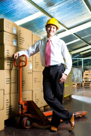 efficiently: Young man in a suit standing besides boxes and packages in a warehouse
