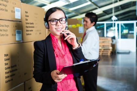 servicio al cliente: Mujer joven en un traje con auriculares en un almac�n, que es del Servicio al Cliente, un compa�ero de trabajo de pie en el fondo