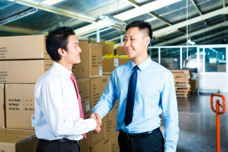 forwarding agency: Manager, owner or businessmen in a warehouse of a forwarding agency or a factory shake hands Stock Photo