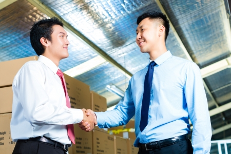 Manager, owner or businessmen in a warehouse of a forwarding agency or a factory shake hands photo