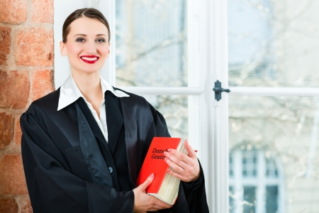 Young female lawyer working in her office reading in a typical law book Stock Photo - 19000698