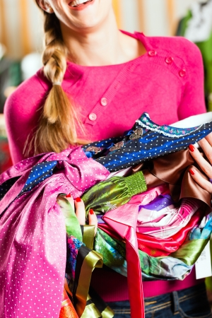 dirndl: Traditional clothes - young woman is buying Tracht or dirndl in a shop, she has lots of dirndl in her arms