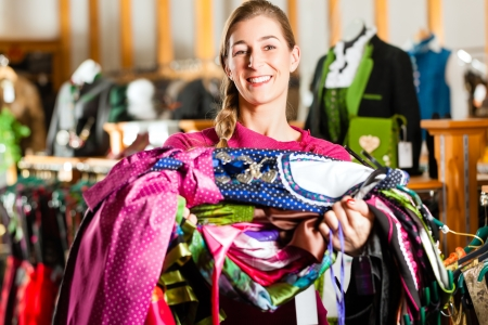 tracht: Traditional clothes - young woman is buying Tracht or dirndl in a shop, she has lots of dirndl in her arms