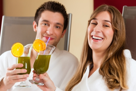 Young couple - man and woman - drinking Chlorophyll-Shake in spa photo