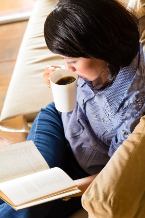 Student - Young asian woman or girl sitting on a sofa with a cup of coffee reading a book, she is learning photo