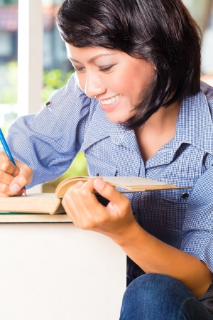 literacy: Student - young woman or girl sitting with books in a library learning, she makes notes Stock Photo