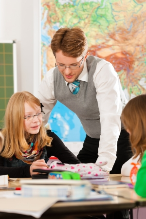 Education - Pupils and teacher learning at elementary or primary school in the classroom Stock Photo