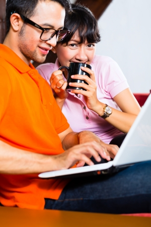 Indonesian couple sitting home on sofa with laptop using the internet for email and online shopping photo