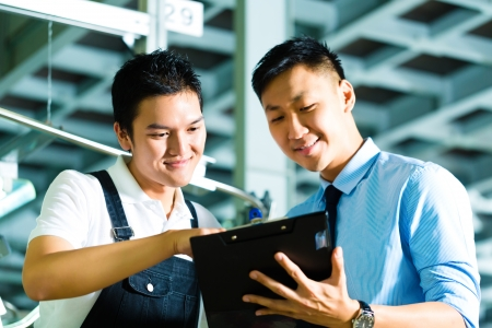 Worker or production manager and owner, ceo or controller, look on a Clipboard in a factory photo