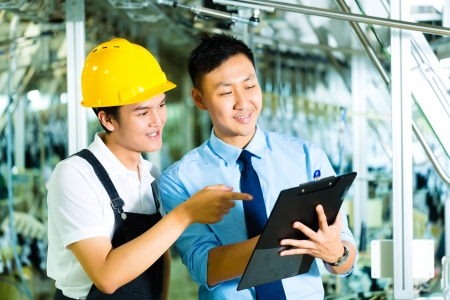 the textile industry: Worker or production manager and owner, ceo or controller, look on a Clipboard in a factory Stock Photo
