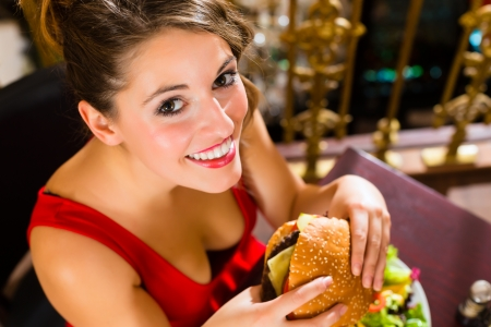 unsuitable: Young woman in a fine dining restaurant eat a hamburger, she behaves improperly