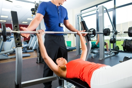 personal trainer: Woman with her personal fitness trainer in the gym exercising with dumbbells, she is using barbell on a weight bench