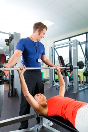 trainer: Woman with her personal fitness trainer in the gym exercising with dumbbells, she is using barbell on a weight bench