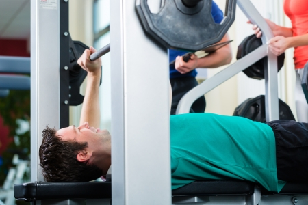 Man with his personal fitness trainer in the gym exercising with dumbbells, he used a barbell on a weight bench photo