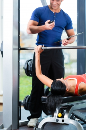 instructor: Woman with her personal fitness trainer in the gym exercising with dumbbells, she used a barbell on a weight bench