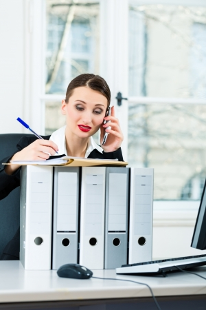 file clerks: Young businesswoman working in her Office, she sits behind folders and on the telephone is a customer or client