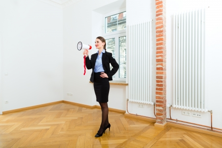 accommodation broker: Young realtor is in an apartment, she makes advertising with a megaphone