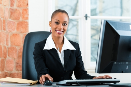 Young female lawyer or paralegal working in her office on a Computer or Pc photo
