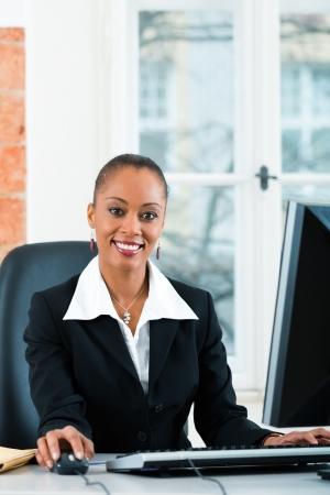 oficinista: Abogado o asistente legal de sexo femenino joven que trabaja en su oficina en un ordenador o PC Foto de archivo
