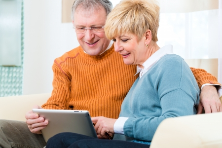 Quality of life - two elderly people sitting at home on the couch and writing emails on the tablet computer Stock Photo - 19226093
