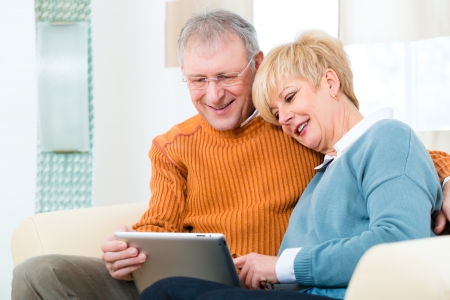 Quality of life - two elderly people sitting at home on the couch and writing emails on the tablet computer Stock Photo - 19226099