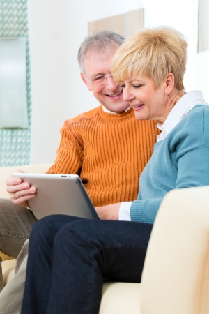 communicative: Quality of life - two elderly people sitting at home on the couch and writing emails on the tablet computer