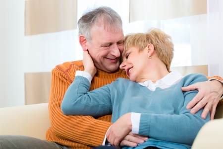 Quality of life - two elderly people sitting at home on the couch, he embraces his wife photo
