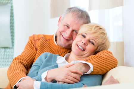 Quality of life - two elderly people sitting at home on the couch, he embraces his wife Stock Photo - 19226083