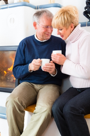 Seniors at home in front of fireplace with tea cup Stock Photo - 19226317