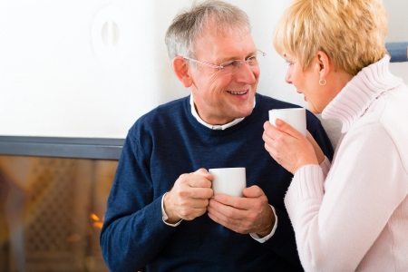 Seniors at home in front of fireplace with tea cup photo