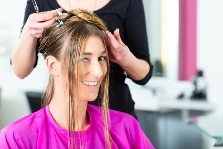 Hairdresser - hair stylist cutting hair, a female customer gets a haircut Stock Photo - 19226104