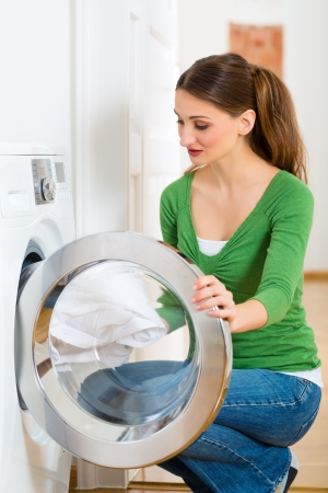 Young woman or housekeeper has laundry day at home, she takes the out of the washing machine or the dryer photo