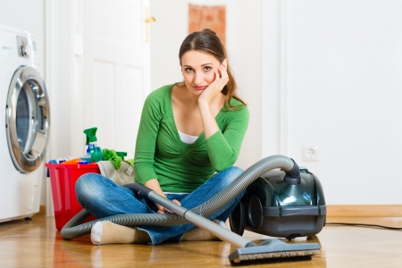 vacuum: Young woman cleaning at home, she has a cleaning day and using a vacuum cleaner cleaning products and a bucket but she does not feel like it