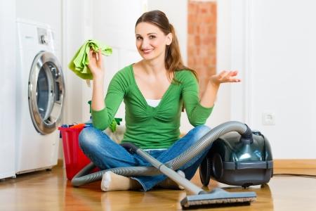 schoonmaakartikelen: Jonge vrouw het schoonmaken in huis, heeft ze een schoonmaak dag en met een stofzuiger reinigingsproducten en een emmer Stockfoto