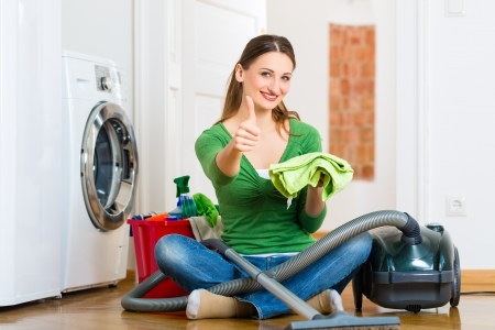 apartment cleaning: Young woman cleaning at home, she has a cleaning day and using a vacuum cleaner cleaning products and a bucket