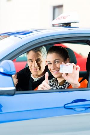 dann: Fahrschule - Junge Frau ein Auto zu lenken, vielleicht hat sie ihre Fahrpr�fung hat, h�lt sie stolz ihren F�hrerschein dann hat sie bestanden Lizenzfreie Bilder