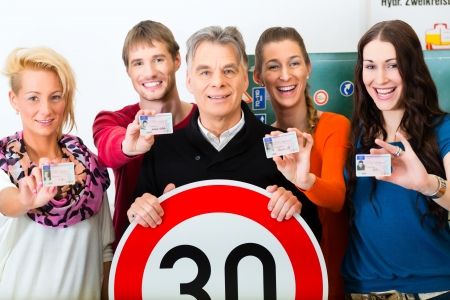 instructors: Driving school - driving instructor and student drivers look at a tempo thirty Road sign, in the background are traffic signs Stock Photo