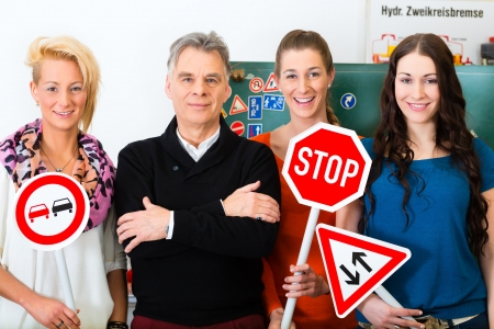 learner: Driving school - driving instructor and student drivers look at a tempo thirty Road sign, in the background are traffic signs Stock Photo