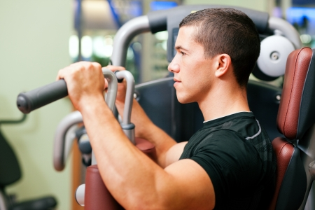 weight machine: Man working out in gym