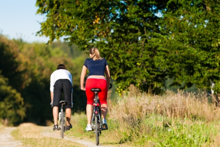 dirt road recreation: Man and woman exercising with bicycle Stock Photo