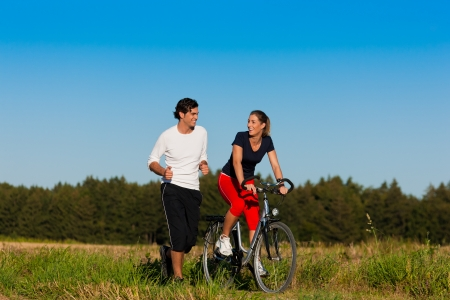 dirt road recreation: Man and woman jogging with bicycle