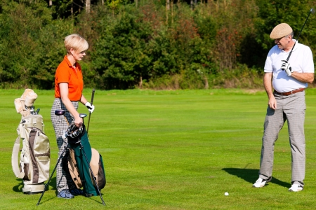 Mature couple playing golf photo