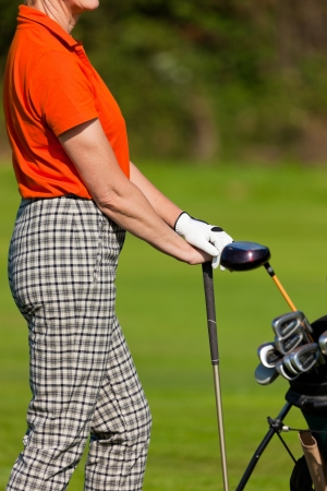 Mature Woman with golf bag playing golf photo