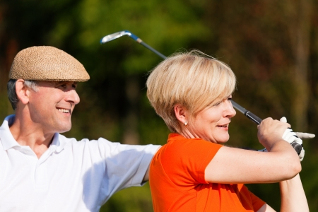 woman golf: Mature couple playing golf