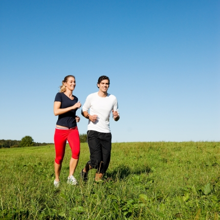 sport couple jogging an meadow in summer photo