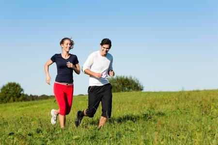 summer sport: sport couple jogging an meadow in summer