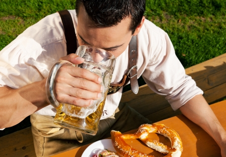 lederhosen: Mann in Lederhosen trinkt Bier