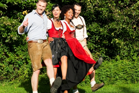 tracht: Group of four friends in Bavarian Tracht dancing Stock Photo