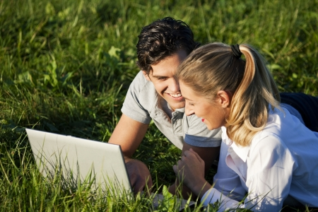 Couple on meadow using wi-fi for Internet photo
