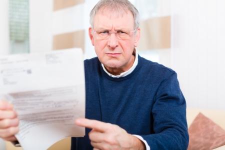 factura: Hombre mayor o cuarto a�o han recibido una carta, tal vez es un recordatorio o un proyecto de ley Foto de archivo